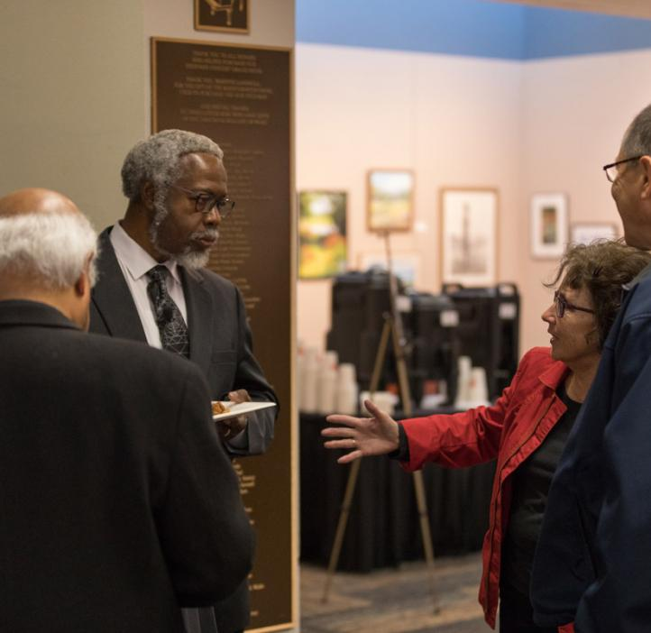 """Sylvester James """"Jim"""" Gates, Jr. chatting with colleagues in lobby"""