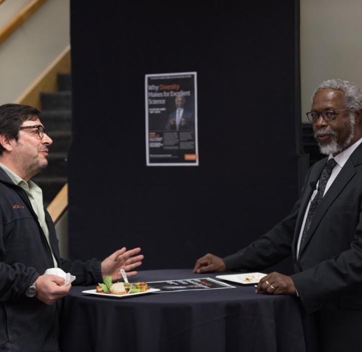 "Sylvester James ""Jim"" Gates, Jr. chatting with Juan Restrepo at table"