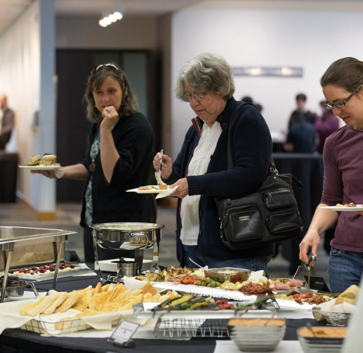 faculty grabbing food at event table