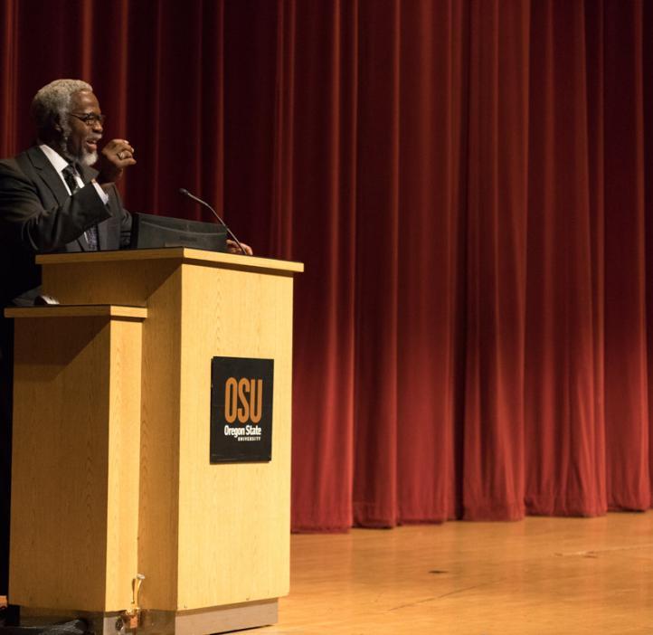 """Sylvester James """"Jim"""" Gates, Jr. spraking on stage behind podium"""