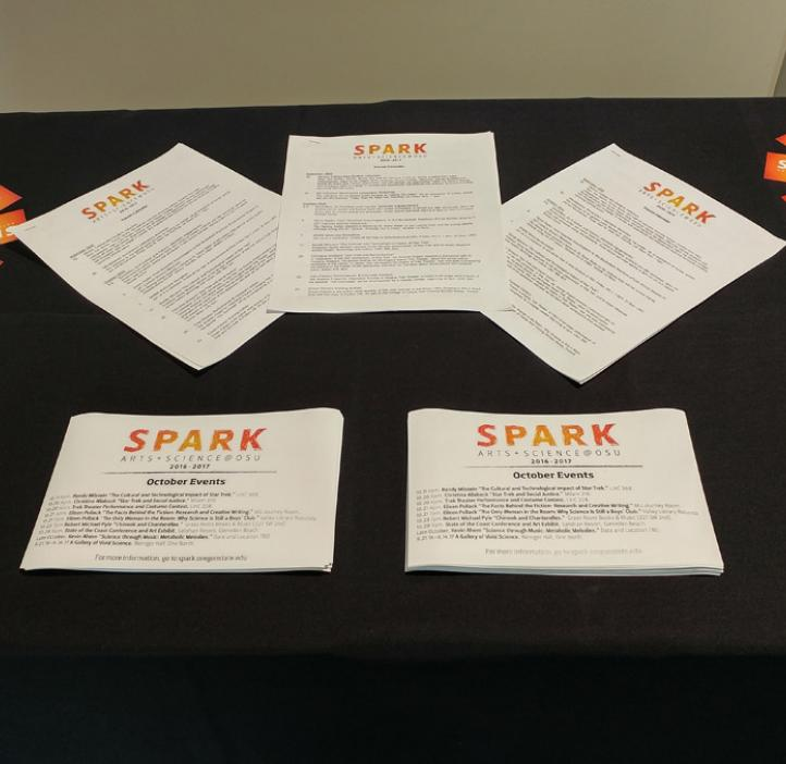 SPARK event flyers and cards on display at table