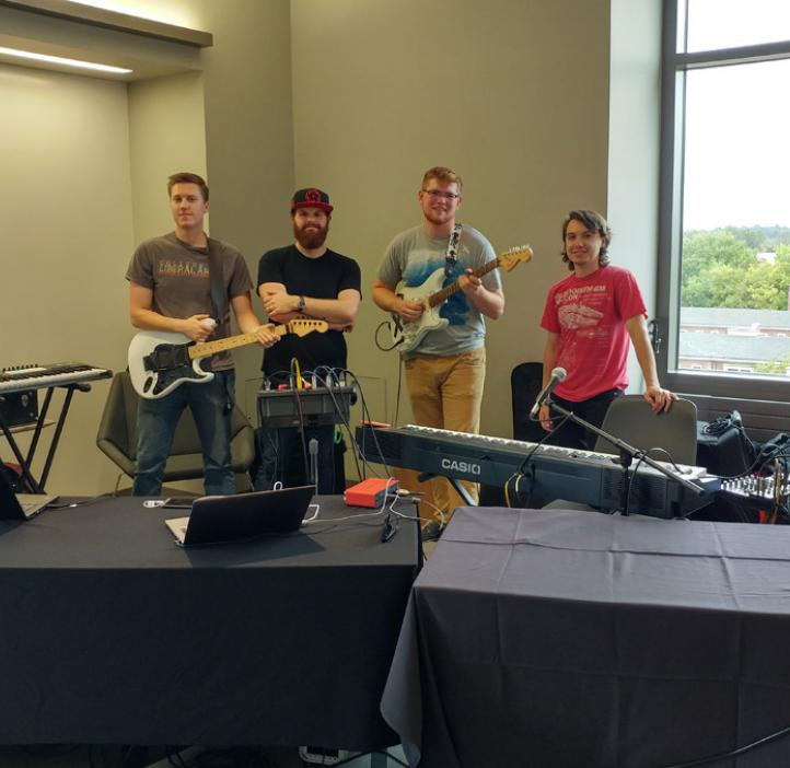 male band with equipment in corner