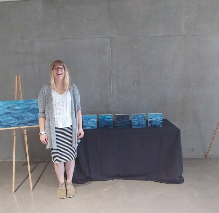 Abigail Losli standing with her paintings