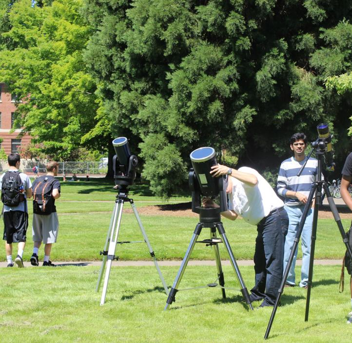 students and faculty looking though telescopes in Valley Library field