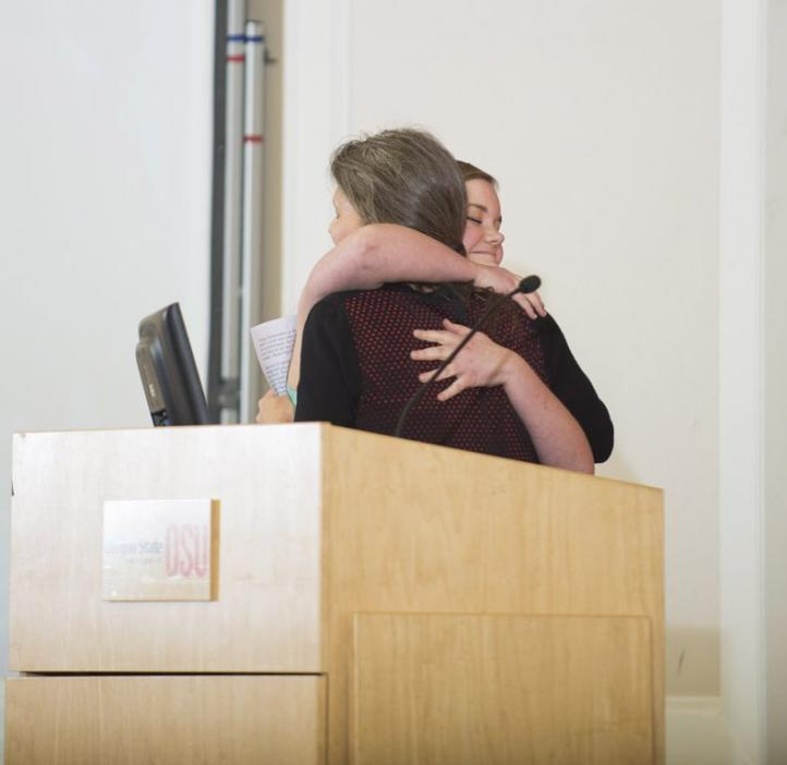 two women hugging from podium