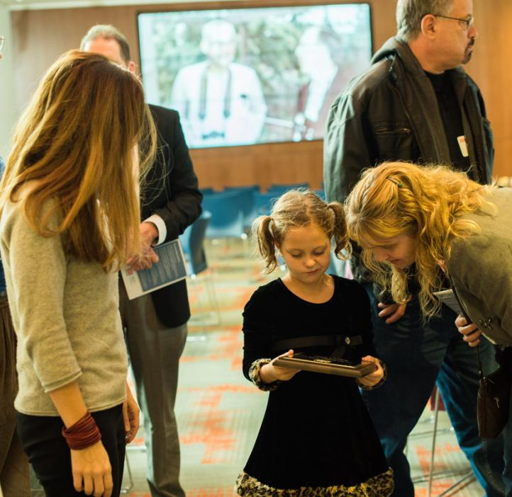 young girl looking at award with mother and sister