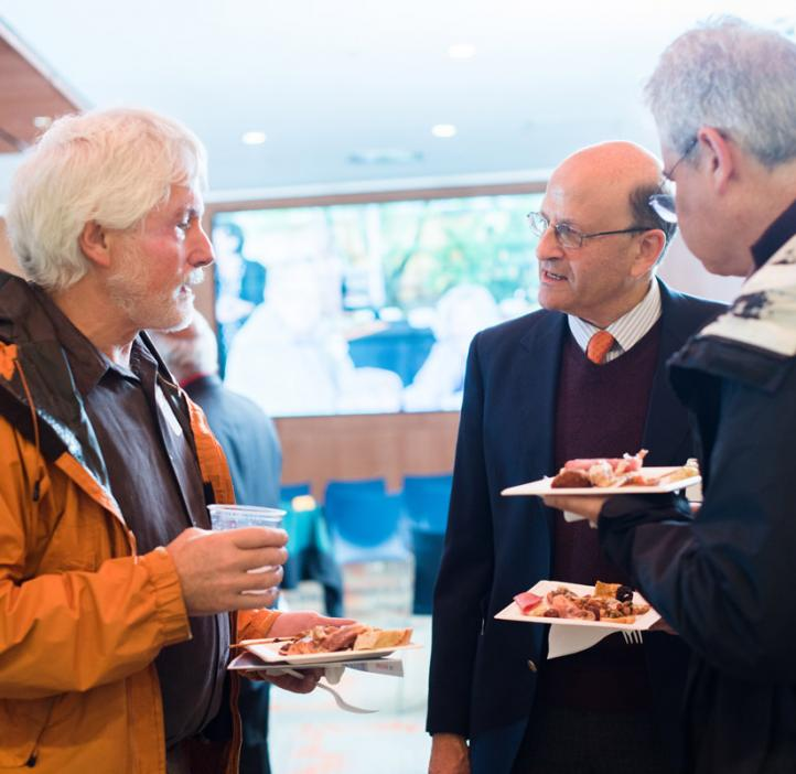 Male science faculty talking over food