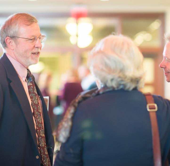 Robert Mason talking with faculty