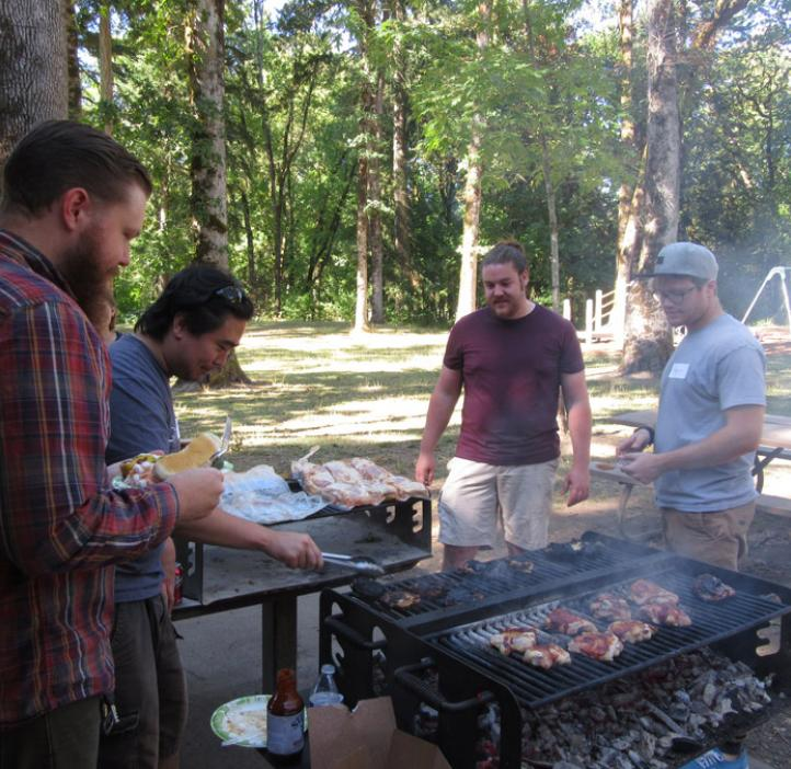 male colleagues grilling chicken