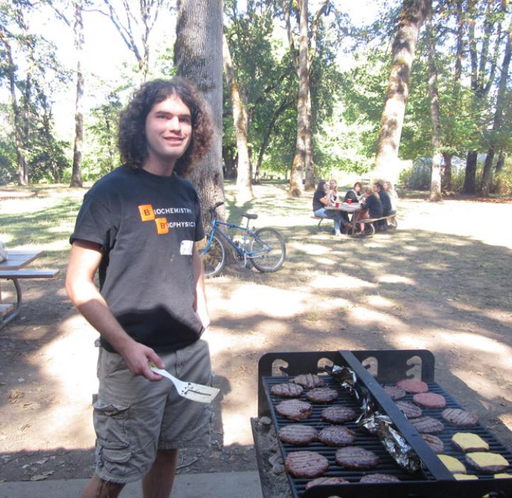 male student grilling burgers