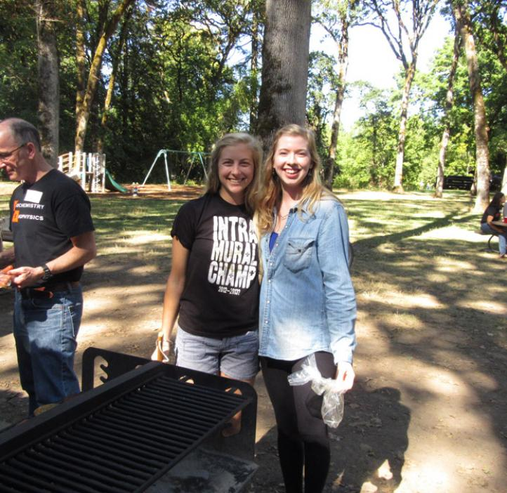 two female student hugging next to grill