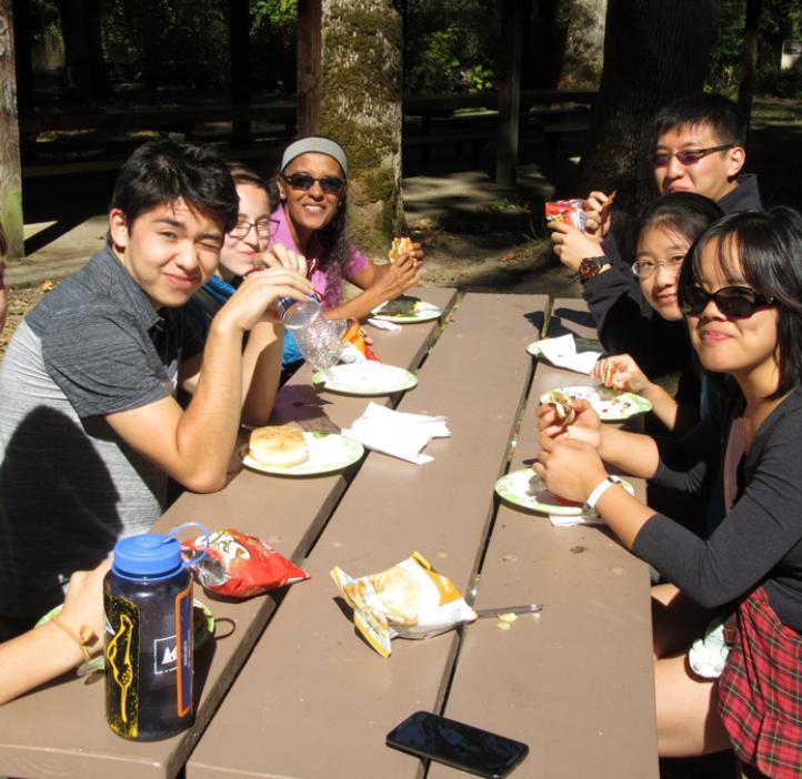 Indira Rajagopal with science students at picnic table