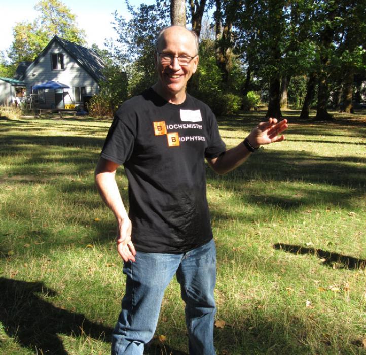 Andy Karplus standing in field wearing wet shirt