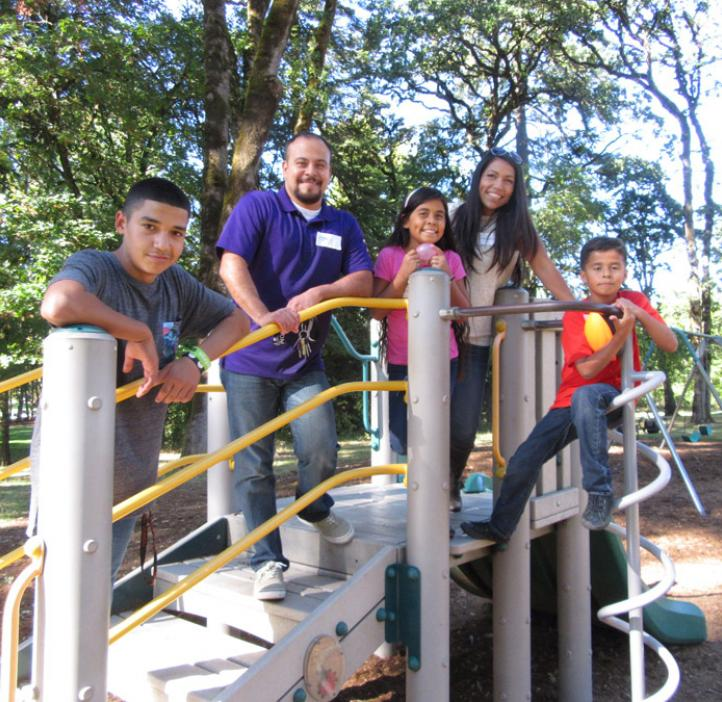 family standing on play structure