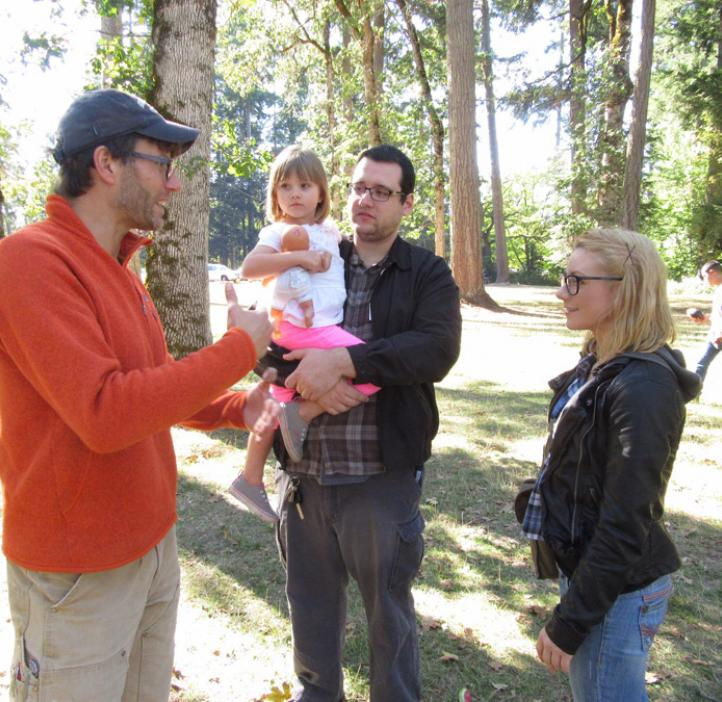 Ryan Mehl talking with colleagues and baby girl