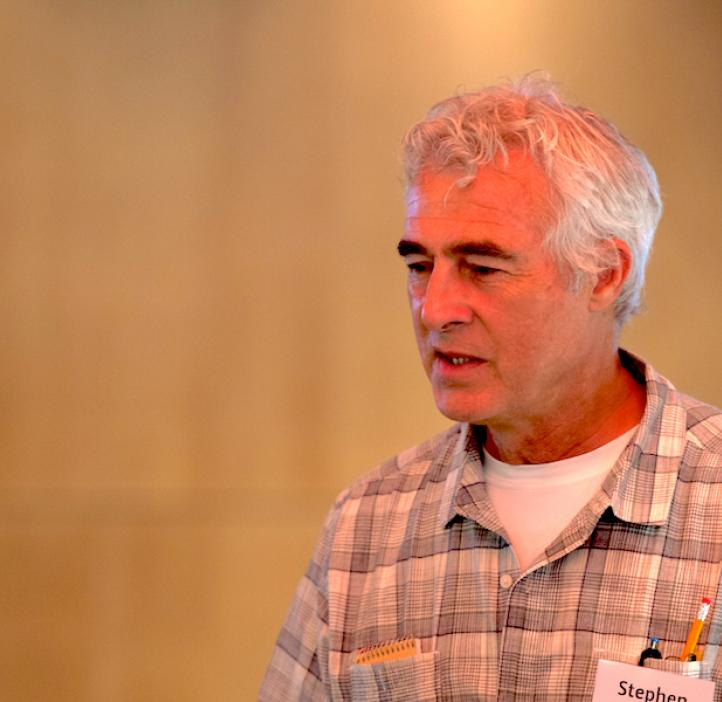 Steve Giovannoni, Distinguished Professor of Microbiology, in front of beige backdrop