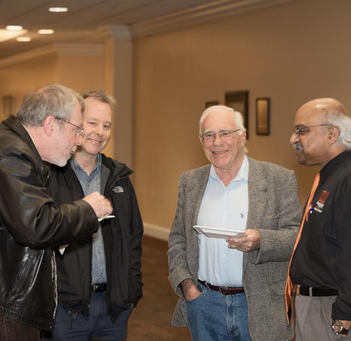 Male science faculty talking in hallway