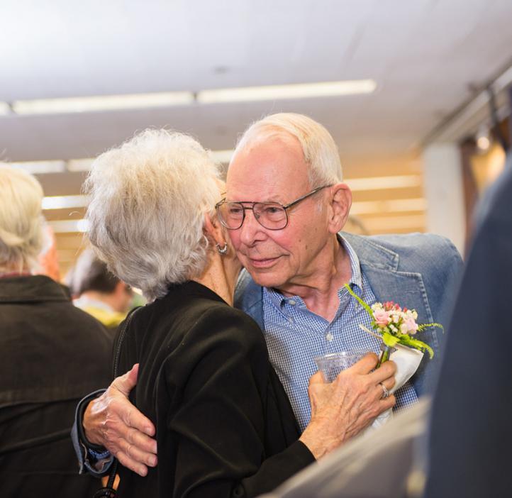 elderly colleagues hugging