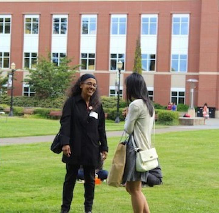 Indira Rajagopal talking with student in Valley Library field