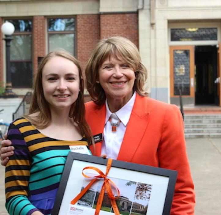 Rochelle Glover with Kathy Bickel holding frame in front of Kidder Hall