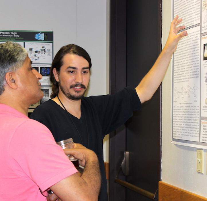 male student presenting poster to colleague