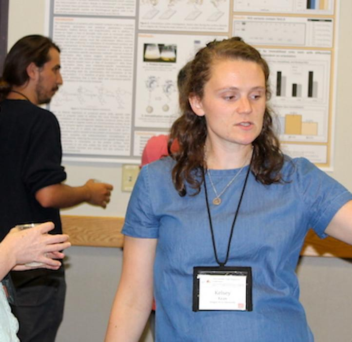 female student presenting poster to female attendee