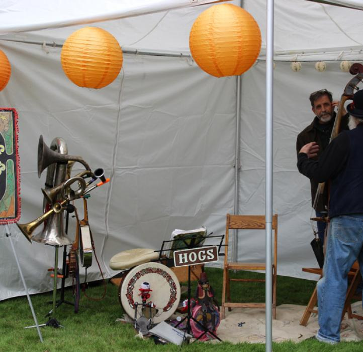 band setting up instruments under tent