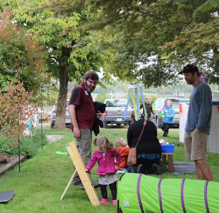 children playing with obstacles with parents
