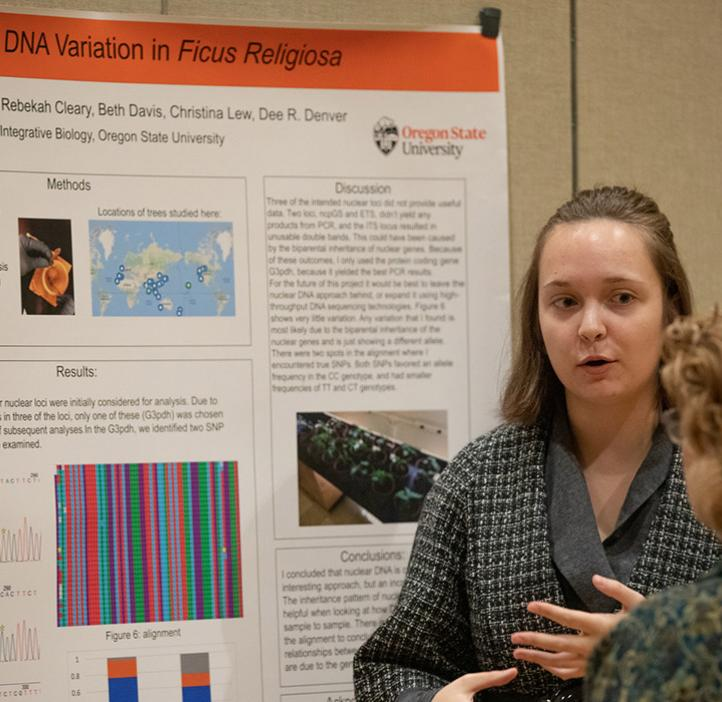 female student showing faculty her research poster