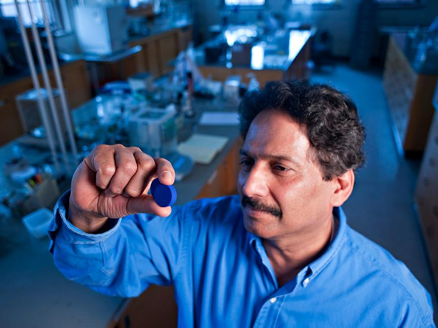 Mas Subramanian holding blue pigment in lab