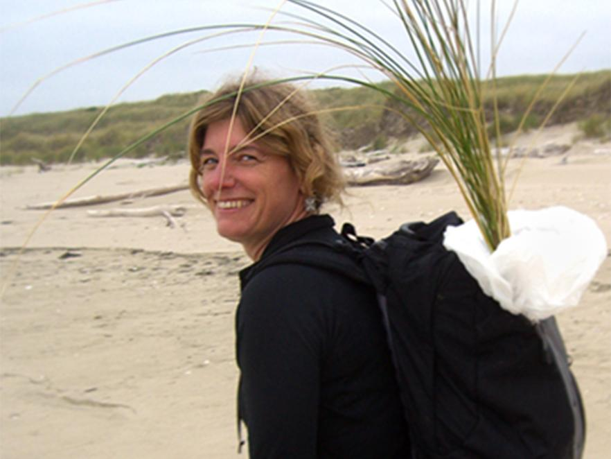 Sally Hacker walking along beach with grass samples in backpack