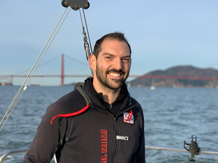 Kenton Hokanson standing on boat in front of the golden gate bridge.