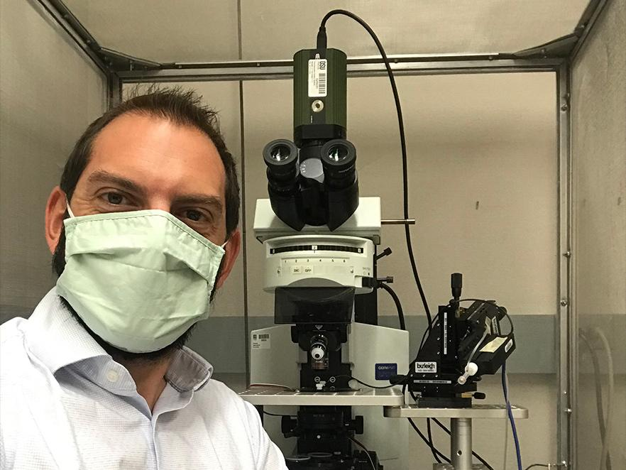 Kenton Hokanson sitting in front of lab equipment with a mask on.