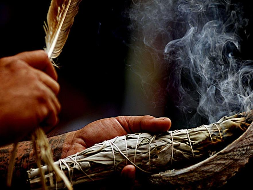 Hands performing a smudging ceremony.